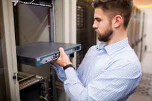 Technician removing server from rack mounted server in server room