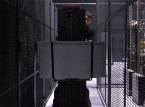 Technician transporting larger server inside a data center.